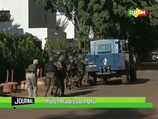 """In this TV image taken from Mali TV ORTM, Security forces approach the Radisson Blu Hotel  hotel in Bamako, Mali, Friday Nov. 20, 2015.  Men shouting """"God is great"""" and armed with guns and throwing grenades stormed into the Radisson Blu Hotel in Mali's capital Friday morning. (Mali TV ORTM,  AP)"""
