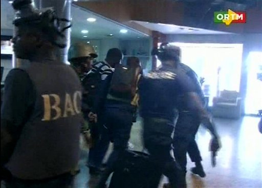 """In this TV image taken from Mali TV ORTM, security forces help hostages to safety, inside the Radisson Blu Hotel in Bamako, Mali, Friday Nov. 20, 2015.  Men shouting """"God is great"""" and armed with guns and throwing grenades stormed into the Radisson Blu Hotel in Mali's capital Friday morning. (Mali TV ORTM, AP)"""
