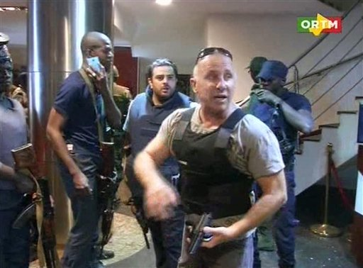 """In this TV image taken from Mali TV ORTM, a security officer gives instructions to other security forces inside the Radisson Blu Hotel in Bamako, Mali, Friday Nov. 20, 2015. Men shouting """"God is great"""" and armed with guns and throwing grenades stormed into the Radisson Blu Hotel in Mali's capital Friday morning. (Mali TV ORTM, AP)"""