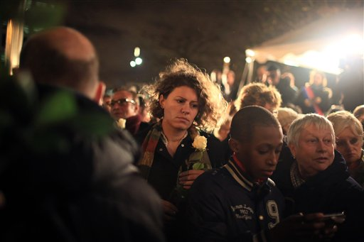 A woman holds a flower during a rally outside the Stade de France stadium, in Saint-Denis, north of Paris, Thursday, Nov. 19, 2015. (AP Photo/Thibault Camus)