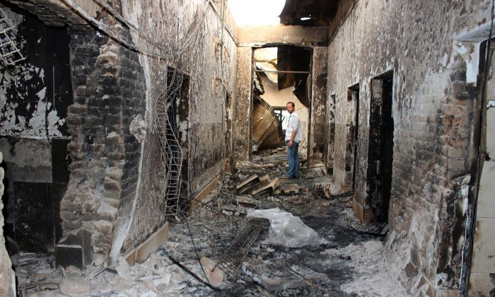 An employee of Doctors Without Borders stands inside the charred remains of their hospital after it was hit by a U.S. airstrike in Kunduz, Afghanistan, on Oct. 16, 2015. (Najim Rahim via AP)