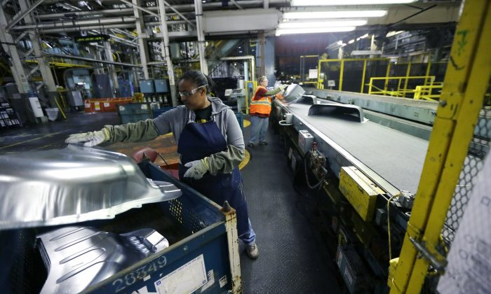 United Auto Workers line worker Michelle Albritton loads stamped wheel housings at the General Motors Pontiac Metal Center in Pontiac, Mich., on April 30, 2015. United Auto Workers union has reached a tentative contract agreement with Ford on Friday, Nov. 6, 2015, a sign that union leaders expect GM workers to approve a similar four-year deal. Voting at GM plants was scheduled to end Friday evening. (AP Photo/Carlos Osorio)