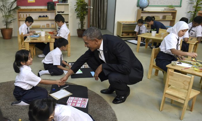 President Barack Obama (C) shakes hands with a girl as he tours the Dignity for Children Foundation in Kuala Lumpur, Malaysia, Saturday, Nov. 21, 2015. Obama visited the center in Malaysia that helps lower income families including refugees, casting a spotlight on the plight of those fleeing violence and persecution from Burma to Syria. (AP Photo/Susan Walsh)