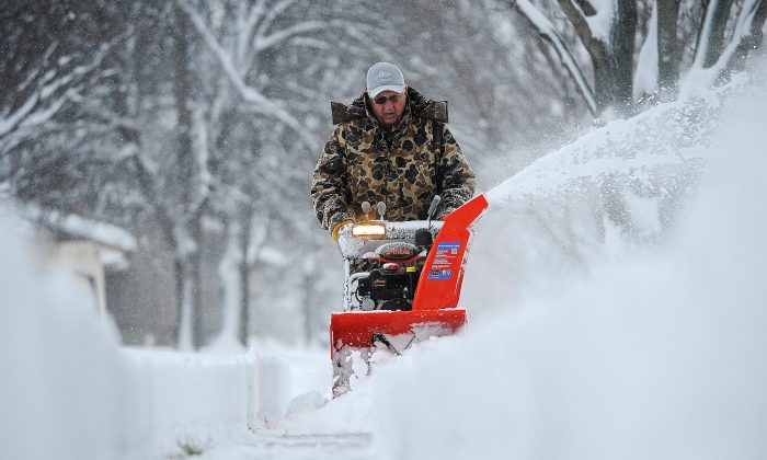 Harvey Wollman uses a snow blower to clear the sidewalk near his house during the first snow of the season Friday, Nov. 20, 2015, in Sioux Falls, S.D. (Joe Ahlquist/The Argus Leader via AP)