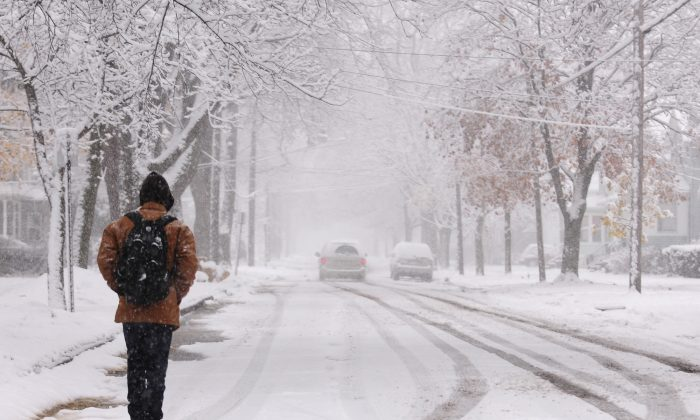A man walks down a snowy street in Jackson, Mich., Saturday, Nov. 21, 2015. The first significant snowstorm of the season blanketed some parts of the Midwest with more than a foot of snow and more was on the way Saturday, creating hazardous travel conditions and flight delays. (Jessica Christian/Jackson Citizen Patriot via AP)