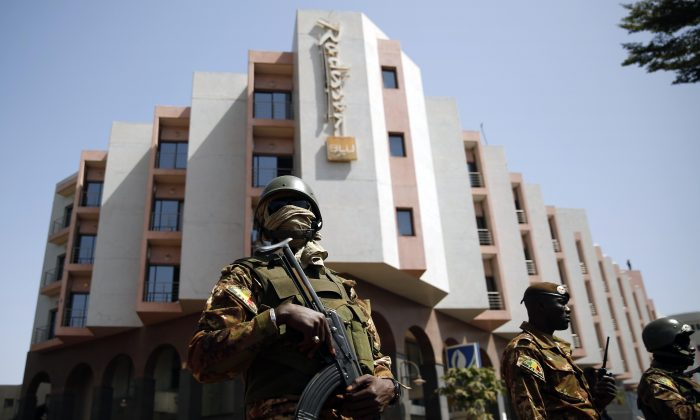 Tight security surrounds Malian President Ibrahim Boubacar Keita as he visits the Radisson Blu hotel in Bamako, Mali, on Nov. 21, 2015. (AP Photo/Jerome Delay)