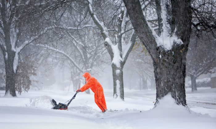 Gary Miller clears his neighbor's driveway after Friday's snowstorm in Janesville, Wis., on Saturday, Nov. 21, 2015. (Anthony Wahl/The Janesville Gazette via AP)