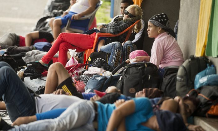 Cuban migrants rest outside the Costa Rican immigration building at the border with Nicaragua, in Penas Blancas, Costa Rica, on Nov. 16, 2015. A surge of some 2,000 Cuban migrants trying to cross Central America to reach the United States triggered a diplomatic spat between Costa Rica and Nicaragua Monday, plunging tense relations between the two countries to a new low. (AP Photo/Esteban Felix)