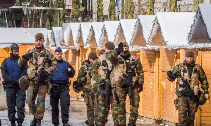 Belgian Army soldiers and policemen patrol near Christmas stalls in the center of Brussels on Sunday, Nov. 22, 2015. (AP Photo/Geert Vanden Wijngaert)