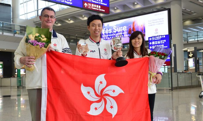 (L-R) Mike Seymour (coach), world champion Wu Siu Hong and Milki Ng (Hong Kong's representative in the Women's event) arriving back in Hong Kong on a flight from Los Angeles, early on Sunday Nov 22, 2015 following Wu's success in winning the 51st Qubica AMF, Bowling World Cup in Las Vegas. (Bill Cox/Epoch Times)