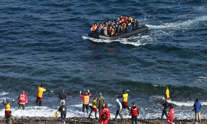 Aid workers gesture at a migrant boat as it approaches shore after making the crossing from Turkey to the Greek island of Lesbos on November 17, 2015 in Sikaminias, Greece. (Carl Court/Getty Images)