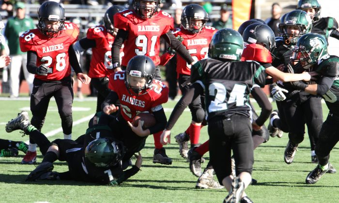Jared Demarco, number 22 with the  Port Jervis Raiders, runs with the ball for a first down during the division II Orange County Youth Football League Superbowl in Newburgh on Nov. 21, 2015. (Rob Waligroski)