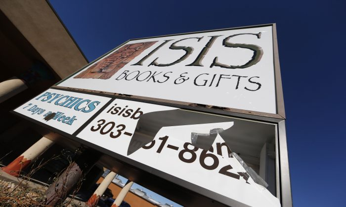 A panel of the sign outside Isis Books and Gifts store is broken Wednesday, Nov. 18, 2015, in Englewood, Colo.  Harrison and his wife, Karen, say that the New Age bookstore has been targeted by vandals because of the shop's name. The owner says the store is named after the Egyptian goddess Isis, and says the most recent vandalism is likely in response to Friday's terror attacks in Paris. (AP Photo/David Zalubowski)