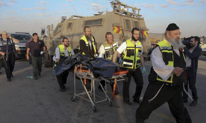 Israeli emergency services evacuate the body of a Palestinian from the scene of an attack near the West Bank Gush Etzion settlements, Sunday, Nov. 22, 2015. The Palestinian, armed with a knife, killed a 21 year old Israeli woman before he was shot and killed by Israeli soldiers. (AP Photo/Mahmoud Illean)