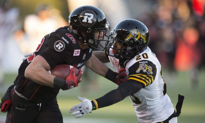 Ottawa Redblacks wide receiver Greg Ellingson fights off Hamilton Tiger-Cats defensive back Emanuel Davis as he runs for a touchdown in the fourth quarter in the CFL East Division final in Ottawa on Nov. 22, 2015. (The Canadian Press/Adrian Wyld)