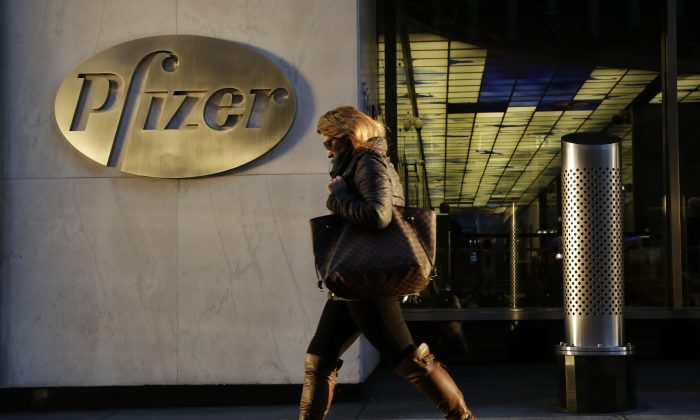 A woman passes Pfizer World Headquarters in New York on Monday, Nov. 23, 2015. Pfizer and Allergan will join in a $160 billion deal to create the world's largest drugmaker. (AP Photo/Mark Lennihan)
