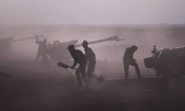 Syrian army personnel load howitzers near the village of Morek, Syria, on Oct. 7, 2015. (Alexander Kots/Komsomolskaya Pravda via AP)
