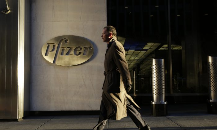 A man walks past Pfizer World Headquarters, Monday, Nov. 23, 2015 in New York. The new tax regulations blocked Pfizer from completing its proposed $160 billion merger deal with Ireland-based Allergan.  (AP Photo/Mark Lennihan)