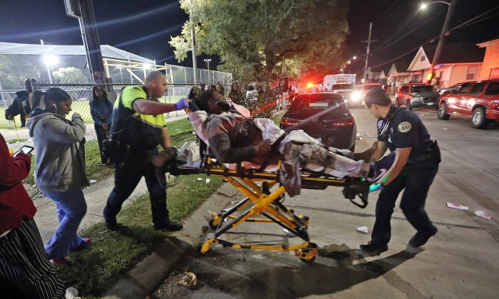 Officials remove a man from the scene following a shooting in New Orleans' 9th Ward on Sunday, Nov. 22, 2015. Police spokesman Tyler Gamble says police were on their way to break up a big crowd when gunfire erupted at Bunny Friend Park. (Michael DeMocker/NOLA.com The Times-Picayune via AP) MAGS OUT; NO SALES; USA TODAY OUT; THE BATON ROUGE ADVOCATE OUT; THE NEW ORLEANS ADVOCATE OUT; MANDATORY CREDIT