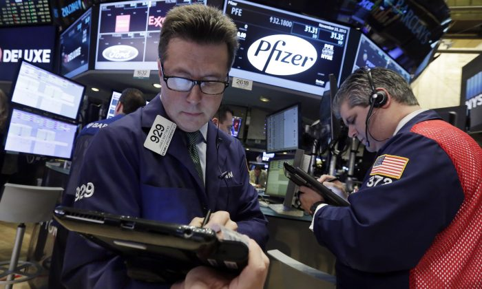 Traders James Matthews (L) and John Panin work at the post that handles Pfizer, on the floor of the New York Stock Exchange on Nov. 23, 2015. (AP Photo/Richard Drew)
