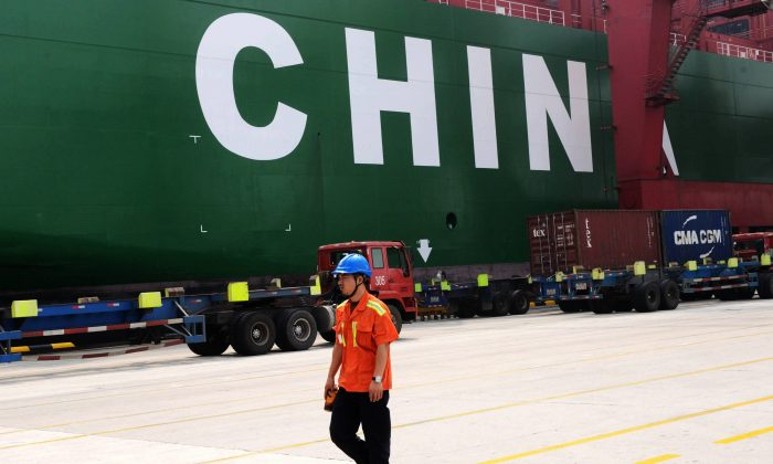A worker walking past a cargo ship in Qingdao port, eastern China's Shandong province, on Oct. 13. (STR/AFP/Getty Images)