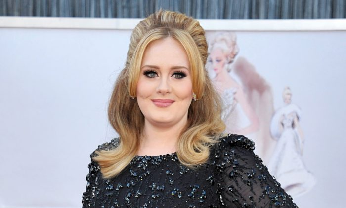 """Singer Adele arrives at the Oscars in Los Angeles on Feb. 24, 2013. Adele's new album """"25"""" has sold more than 2.3 million copies in the United States during its first three days on the market, a stunning number for a music industry that has seen sales steadily fall in the digital era. (John Shearer/Invision via AP)"""