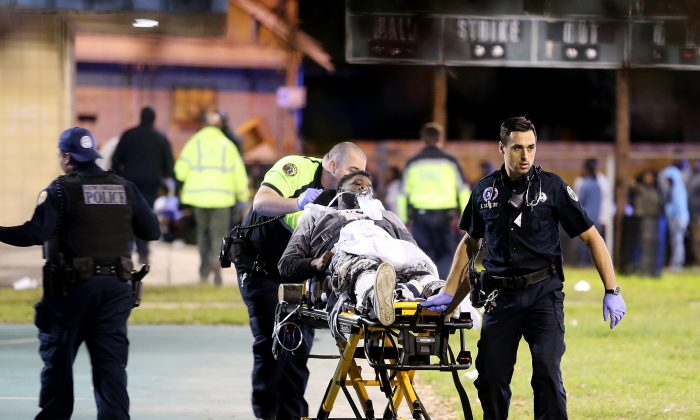 Paramedics with New Orleans EMS remove a person from the scene following a shooting in New Orleans' 9th Ward on Nov. 22, 2015. Police spokesman Tyler Gamble says police were on their way to break up a big crowd when gunfire erupted at Bunny Friend Park. (Michael DeMocker/NOLA.com The Times-Picayune via AP)