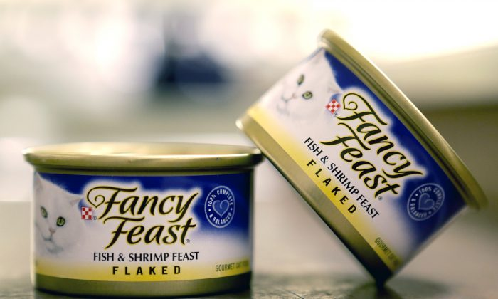 This Nov. 16, 2015, photo shows Fancy Feast cat food, fish and shrimp feast flavor, a product of Thailand, purchased at a Publix market in Orlando, Fla. A report commissioned by Nestle SA found that impoverished migrant workers in Thailand are sold or lured by false promises and forced to catch and process fish that ends up in the global food giant's supply chains. Nestle is not a major purchaser of seafood in Southeast Asia but does some business in Thailand, primarily for its Purina brand Fancy Feast cat food. (AP Photo/John Raoux)