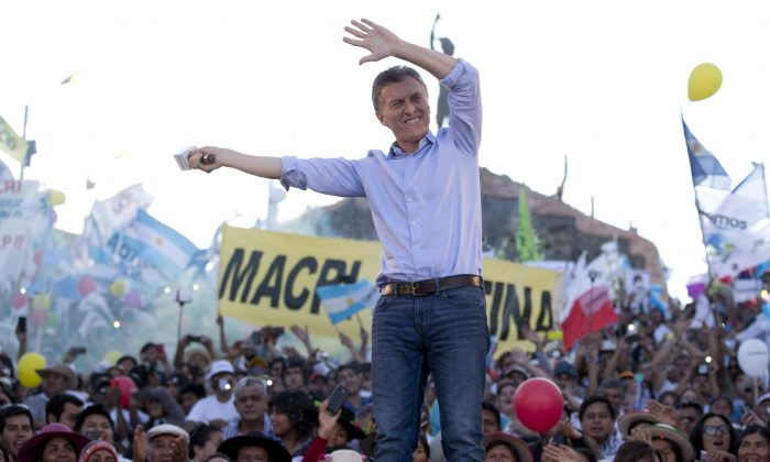 In this Thursday, Nov. 19, 2015 photo, opposition presidential candidate Mauricio Macri waves to supporters during the closing campaign rally in Humahuaca, Jujuy, Argentina. (AP Photo/Natacha Pisarenko)