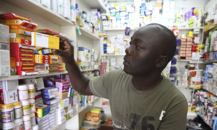 Ayo Bello displays a box of Coartem malaria medication, packaged for the commercial market, at a pharmacy in Lagos, Nigeria, on Aug. 30, 2010. Millions of free malaria drugs are sent to Africa every year by international donors. New research is now providing evidence for what health workers have long suspected: some of the donated medication, readily identifiable by its different packaging, is being stolen and resold on commercial markets. (AP Photo/Sunday Alamba)