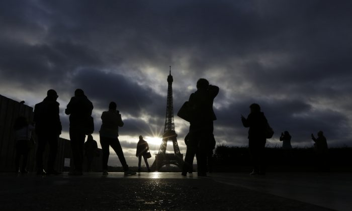 Tourists visit the site of Eiffel Tower which remained closed on the first of three days of national mourning in Paris on Nov. 15, 2015. Thousands of French troops deployed around Paris on Sunday and tourist sites stood shuttered in one of the most visited cities on earth while investigators questioned the relatives of a suspected suicide bomber involved in the country's deadliest violence since World War II. (AP Photo/Amr Nabil)