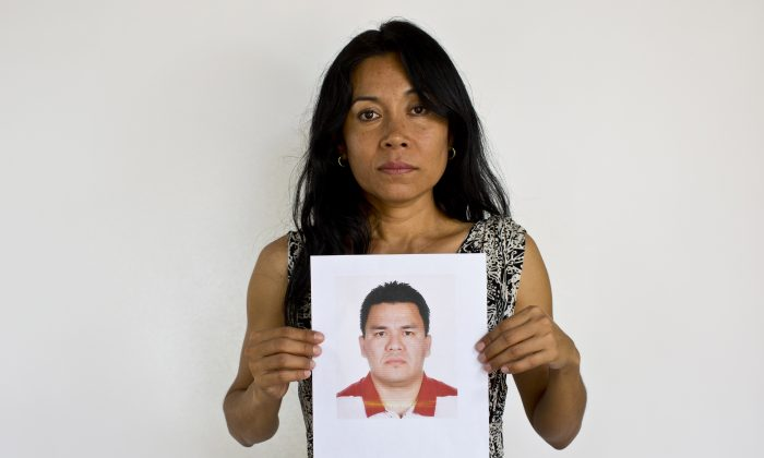 Adriana Bahena Cruz holds up a photo of her husband, Saulo Rodriguez Cruz, in Iguala, Mexico, on May 13, 2015. (AP Photo/Dario Lopez-Mills)