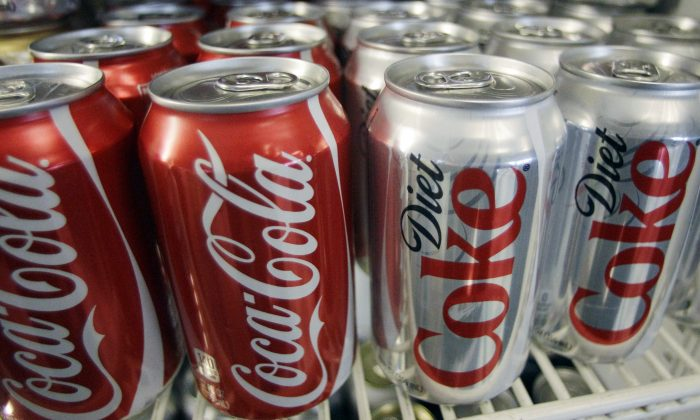In this March 17, 2011, file photo, Cans of Coca-Cola and Diet Coke sit in a cooler in Anne's Deli in Portland, Ore. (AP Photo)