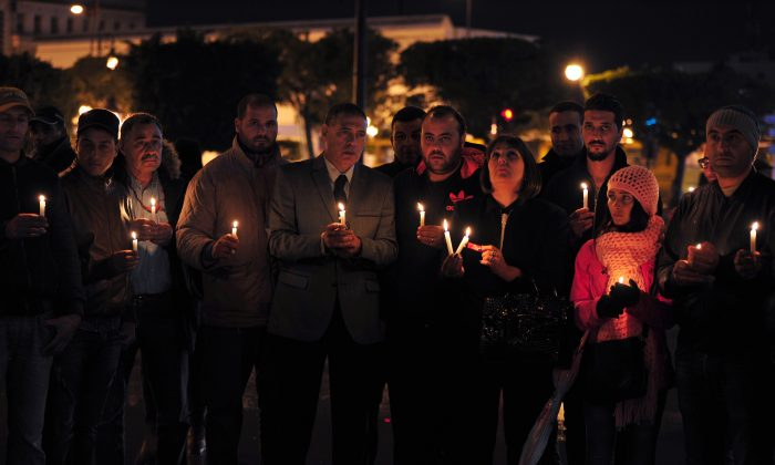 Tunisian Nidaa Tounes party members hold candles during a vigil in Tunis in memory of the victims of a bomb blast earlier in the day on a bus transporting Tunisia's presidential guard in the center of the Tunisian capital on Nov. 24, 2015. (Fethi Belaid/AFP/Getty Images)