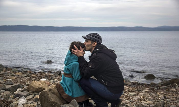 A Syrian man kisses his daughter shortly after disembarking from a dinghy at a beach on the Greek island of Lesbos after crossing the Aegean sea from the Turkish coast, Nov. 16, 2015. Experts say refugees are at a high-risk for mental health issues and often suffer spiked rates of depression and substance abuse. (AP Photo/Santi Palacios)