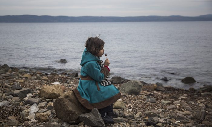 A Syrian girl eats a lollipop after her arrival on a small boat from the Turkish coast on the northeastern Greek island of Lesbos on Nov. 16, 2015. (AP Photo/Santi Palacios)