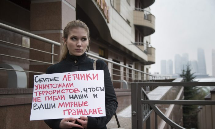 A woman holds a sign as she pickets the Turkish Embassy in Moscow on Nov. 24, 2015. The sign reads : The pilots that were shot down, were fighting with terrorists, to save your and our civilians. (AP Photo/Alexander Zemlianichenko)