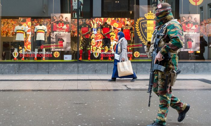 A Belgian Army soldier patrols in a shopping street in the center of Brussels on Wednesday, Nov. 25, 2015. Students in Brussels have begun returning to class after a two-day shutdown over fears that a series of simultaneous attacks could be launched around the Belgian capital. Underground transport in Brussels is also slowly starting up again after a four-day closure. (AP Photo/Geert Vanden Wijngaert)