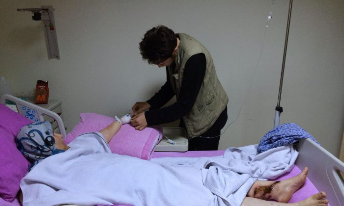 In this picture taken with a mobile phone on Saturday, Oct. 24, 2015, a Syrian boy Abdulhamid Khanfoura, 16, background, helps his wounded mother Zahra Khanfoura, 48, who was burned by a Russian airstrike that hit her house in the central Syrian village of Habeet, as she lies on her hospital bed in the southern city of Kadirli, Turkey. Zahra's granddaughter Raghad was among dozens of civilians who activists say have been killed in the Russian air campaign in Syria, which Moscow says is aimed at crushing the Islamic State group and other Islamic militants. (AP Photo/Hussein Malla)