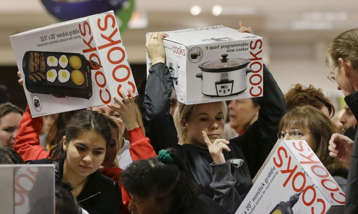 Shoppers rush to grab electric griddles and slow cookers on sale for $8 shortly after the doors opened at a J.C. Penney on the morning of the black Friday in 2012 in Las Vegas.  (AP Photo/Julie Jacobson)