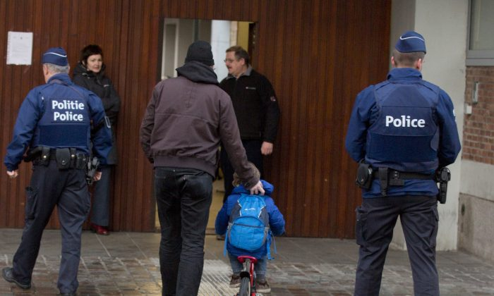 A man wheels a boy on his bicycle past police officers as they arrive for school in the center of Brussels on Wednesday, Nov. 25, 2015. (AP Photo/Virginia Mayo)
