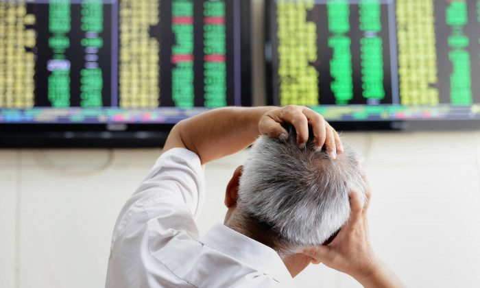 An investor looks at screens showing share prices at a securities firm in Qingdao, in eastern China's Shandong province on August 25, 2015. (STR/AFP/Getty Images)