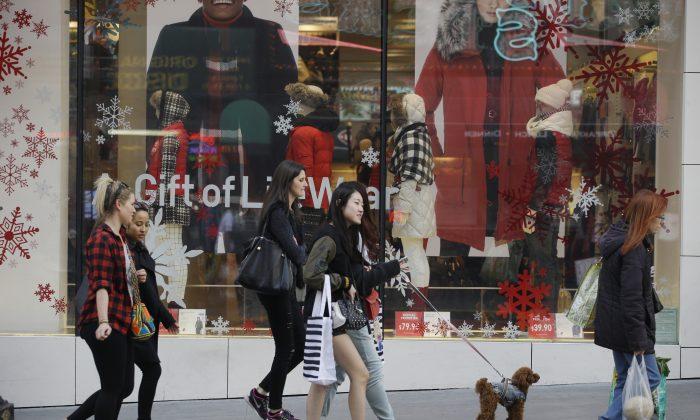 Shoppers walk in front of a holiday display in San Francisco on Nov. 22, 2015. (AP Photo/Marcio Jose Sanchez)