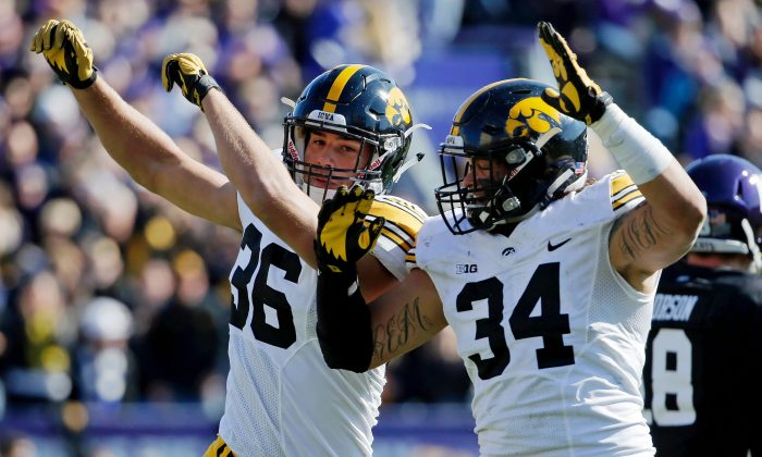 Cole Fisher (L) and Nate Meier of the Iowa Hawkeyes likely need a win over Nebraska to keep their playoff hopes alive. (Jon Durr/Getty Images)