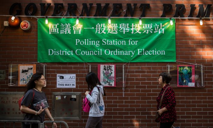 Voters walk past a polling station in the Wan Chai district of Hong Kong on Nov 22, 2015. Hong Kong went to the polls on Nov. 22 for the first time since huge pro-democracy protests gripped the city, in a key test of public sentiment. (Anthony WallaceE/AFP/Getty Images)