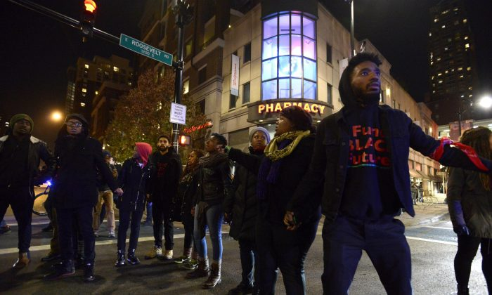 Protesters block a street during a protest for 17-year-old Laquan McDonald in Chicago on Nov. 24, 2015. Chicago police Officer Jason Van Dyke, who shot McDonald 16 times last year, was charged with first-degree murder Tuesday, hours before the city released a video of the killing. (AP Photo/Paul Beaty)