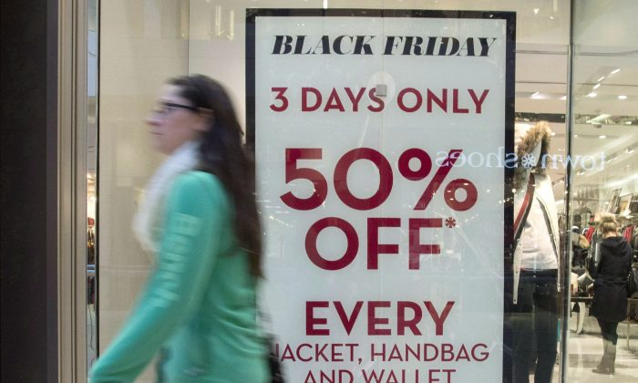 A woman passes a store advertising Black Friday sales at Ottawa's Bayshore Centre in this file photo. (The Canadian Press/Justin Tang)
