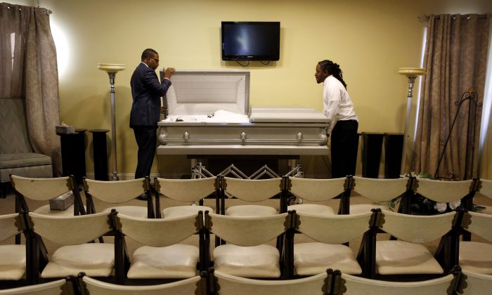 Funeral director John Williams (L) closes a casket containing the remains of a man who died of natural causes in his Baltimore funeral home, on Oct. 16. (AP Photo/Patrick Semansky)