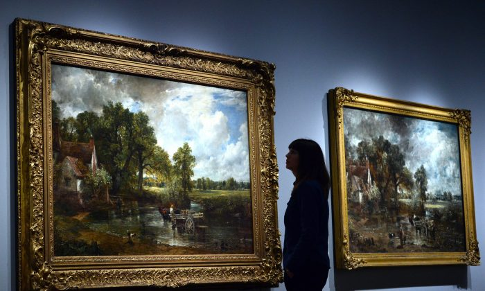 """An employee poses between paintings by British artist John Constable entitled """"The Hay Wain"""" (L) and """"The Hay Wain (full-scale sketch)"""" during a photocall at the Victoria and Albert Museum in London on Sept. 17, 2014. (Carl Court/AFP/Getty Images)"""