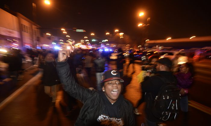 Protesters march during a demonstration, Tuesday, Nov. 24, 2015, for 17-year-old Laquan McDonald, who was fatally shot and killed in October 2014, in Chicago. (AP Photo/Paul Beaty)